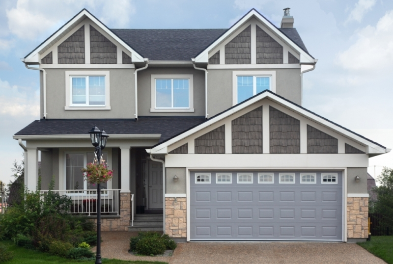 New two-storied gray home with garage on first floor.