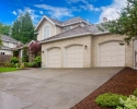Large beige house with three car garage and large driveway.